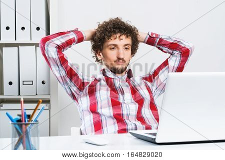 Young relaxed man in checked shirt in his office with hands on head