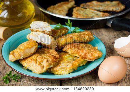 Fish fillet fried in egg batter on a wooden background