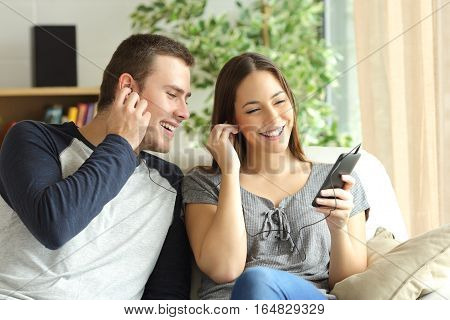 Happy couple listening music and sharing earphones sitting on a sofa in the living room at home