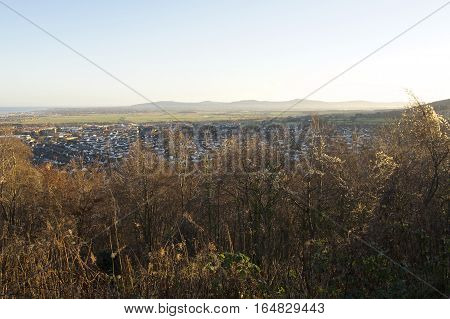 Overlooking Small town surrounded by countryside with mountainous background, British Village quaint in winter framed by plants