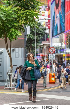 Hong Kong, China - December 6, 2016: a typical Asian woman writing with smart phone a message along Causaway Bay street market Jardine's Crescent, world famous for luxury shopping centers.