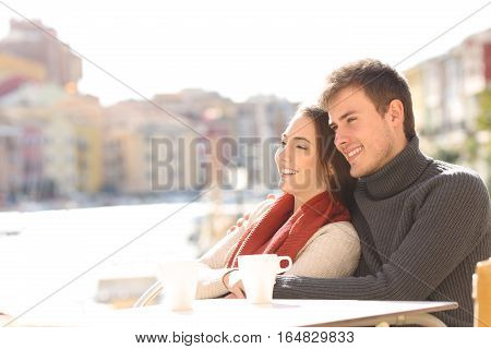 Couple relaxing sitting in an hotel terrace on holidays with a port in the background in a sunny day of winter
