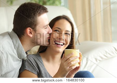 Happy husband kissing his wife in the living room at home. Happy couple concept