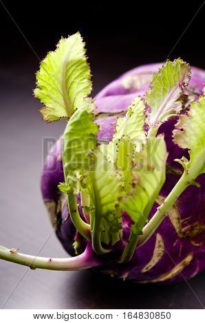 Purple kohlrabi cabbage with green leaves on dark wooden table, vertical
