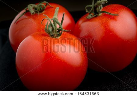 Three red ripe tomatoes on black background