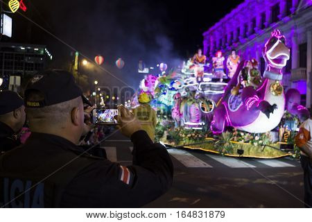 SAN JOSE, COSTA RICA - December 18: Policeman taking photos of a Christmas parade float based on The Flintstones during the Festival of Light Parade whichl is part of Christmas and holiday season Festivities in Costa Rica. December 18, 2016 in San Jose