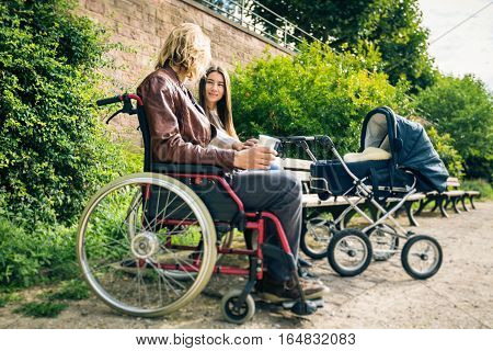 Young parents father sitting in wheelchair enjoying time outdoors, taking their baby to a park along the banks of the river Neckar in Heidelberg, Germany.