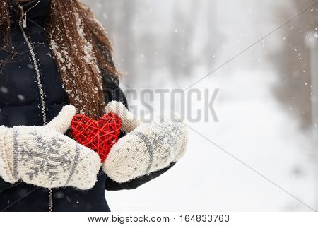 Woman holding red rattan heart on winter snow background, Valentines Day concept.