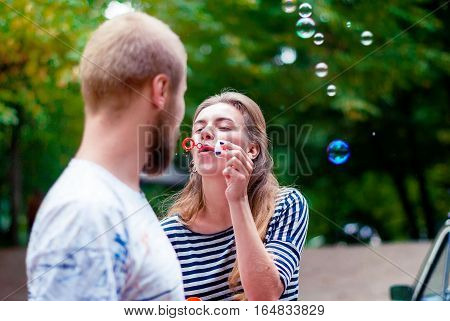 Young girl with soap bubbles and a guy with a beard. Happy woman holding soap bubbles soap bubbles.