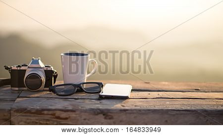 Cup with tea on table over mountains landscape with sunlight vintage. Beauty nature background
