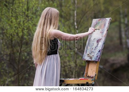 artist girl with long white hair painting a picture in nature plein air painting on the easel brush in hand spring background a woman in a dress
