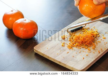 Mandarin zest on wooden board with couple of mandarins alongside
