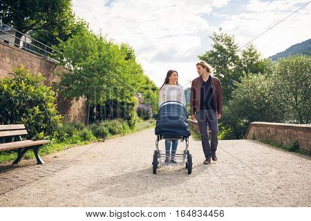 Young parents enjoying time outdoors, taking their baby to a park along the banks of the river Neckar in Heidelberg, Germany.