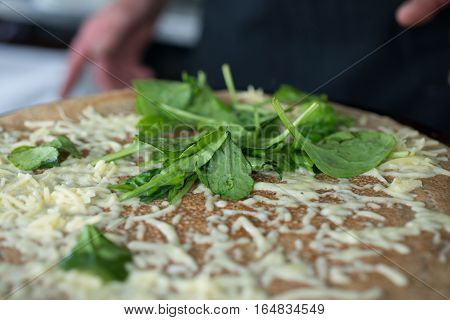 Cheese crepe cooking topped with leafy greens