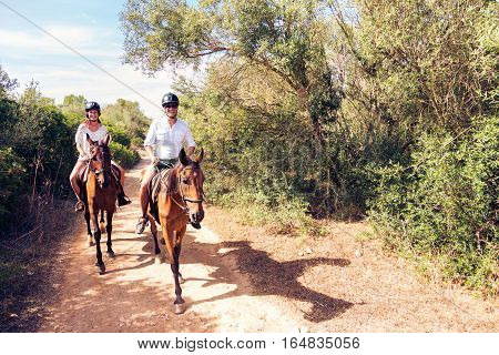 Young tourist couple horseback riding in Mallorca, Spain.