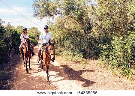 Young tourist couple horseback riding in Mallorca, Spain.