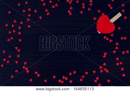 Red heart and many small hearts on the dark wooden background. Empty space for text or photo. Picture frame. Valentines Day card. Valentine's theme. Copy space.
