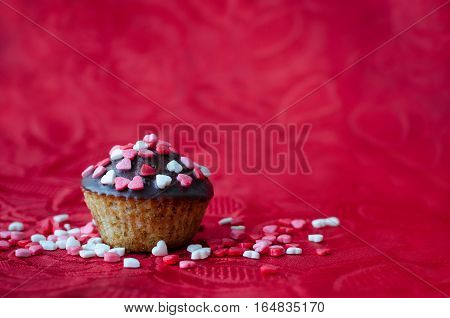 Cupcakes with chocolate and small hearts on red backdrop with space for text. Romantic love concept. Valentine's day card. Valentines background. Copy space. Selective focus.