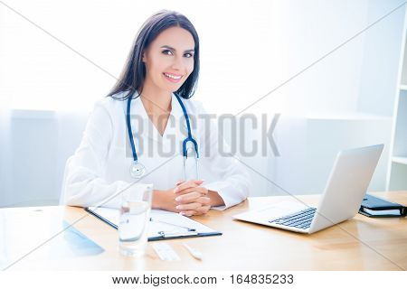 Portrait Of Cheerful Happy Female Doctor On Consultation