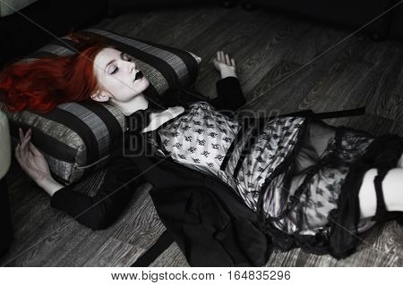 Portrait of red-haired girl in bow tie on a dark background gothic style girl in a black dress sense of fashion style girl in dress and in a black cloak black coat black lips girl lies legs