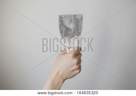 working tool spatula in hand on a light background work plasterer painter to make repairs