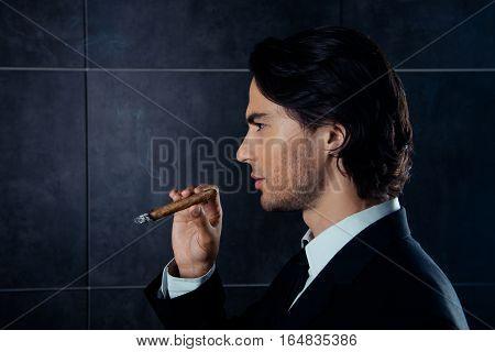 Side view portrait of brutal handsome man holding a cigar