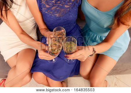 Top view of three women clinking with glasses of shampagne