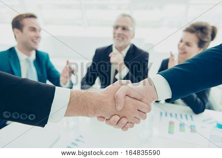 Close up of two businessmen shaking hands above signed contract