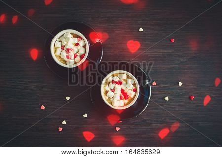 Two cup of coffee with marshmallow and small hearts. Breakfast on Valentine's Day for couple. Romantic love background. Valentines theme. Top view.