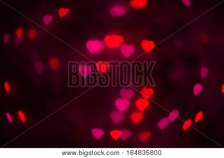 Pink and red hearts bokeh in dark texture for use in graphic design. Valentines style defocused lights background. St. Valentine's Day.