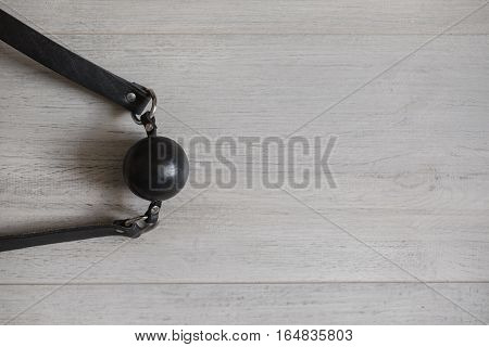black gag on the wooden floor, sex toy