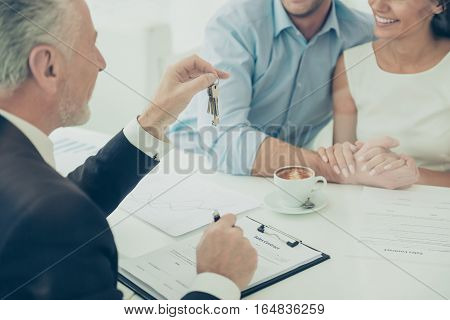 Close Up Of Real Estate Agent Giving Keys To Couple Of Customers