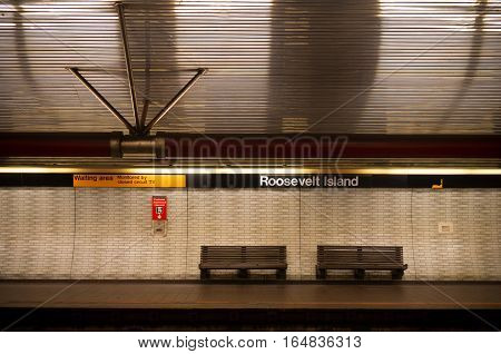 double bench on an empty roosevelt island subway platform