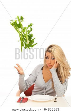 young blond woman is not quite eager to have some healthy celery stalks