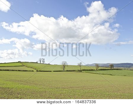 Idyllic British countryside England and Wales UK, rolling hills, fields and blue sky with white cloud, summer.