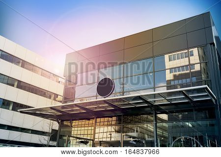 Blank black round signage mockup, modern business building. Circle sign board mock up hanging on glass roof of the store endrance. Street advertising banner design template.