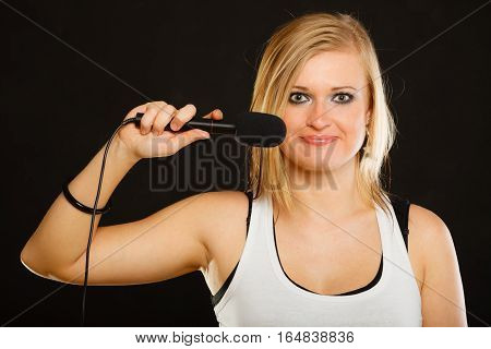 Karaoke music singer concept. Portrait of blonde woman singing to microphone young star performing studio shot black background.