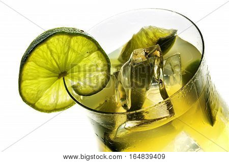 View in a cocktail glass fresh mixed drink with lime and ice alcohol free isolated on a white background selected focus narrow depth of field