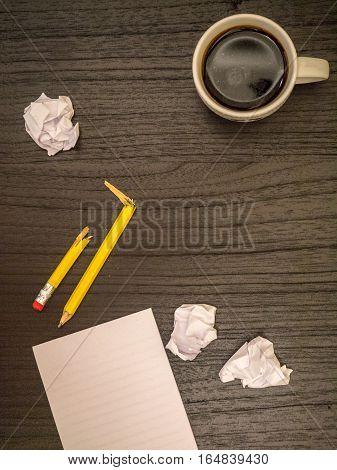 Dark surface paper wads broken pencil coffee frustration