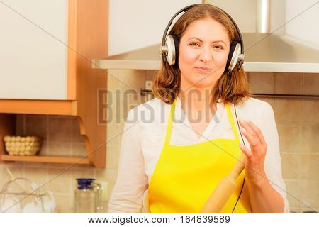 Cooking and preparing food concept. Happy relaxed beauty woman housewife chef with earphones listening music in house kitchen making dinner meal.