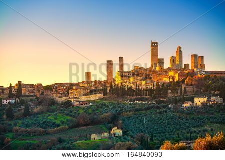 San Gimignano town skyline and medieval towers sunset. Italian olive trees in foreground. Tuscany Italy Europe.