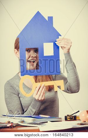 Ownership property security safety lock concept. Blonde girl looking through window. Young lady holding house model key cutout.
