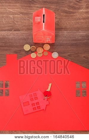 Housing property finances ownership rent mortgage concept. Home cutout with keys. House symbol together with keyring coins.