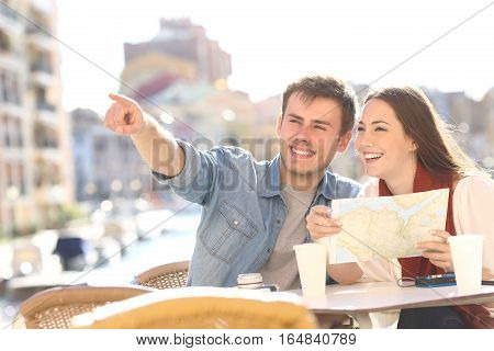 Couple of tourists searching location siting in an hotel terrace during a summer travel with a port in the background