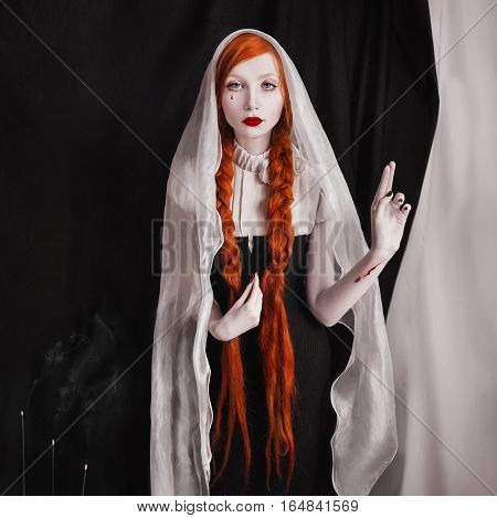 red-haired girl with red lips and pale skin and tear on cheek a woman with long red hair tied in braids with a veil on head cuts on hand a black gothic clothes smoke of incense black background