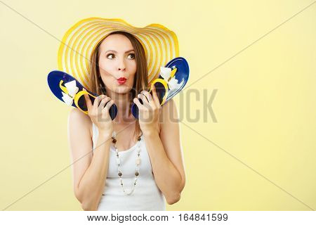 Holidays summer fashion concept. Woman in big yellow hat holding flip flops in hand bright background.