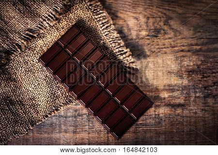 Dark Chocolate bar on dark old wooden background / chocolate bar pieces