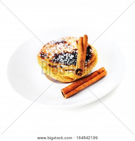 Heap of egg tarts isolated on white background close up / Typical portuguese dessert pasteis de nata with cinnamon sticks