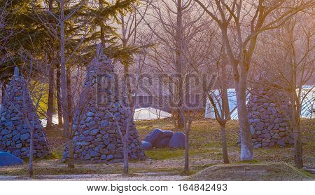 Three stone columns build in the shape of upside down cones surrounded by trees