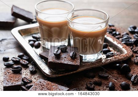 Coffee liqueur shot glasses with homemade baileys roasted coffee beans and chocolate selective focus toned image